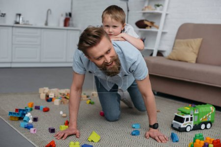 Photo for Smiling father and little son having fun together at home - Royalty Free Image