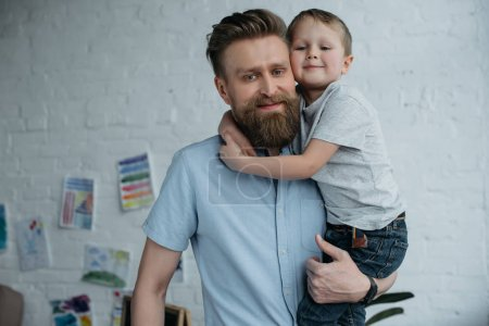 Photo for Portrait of smiling father holding little son and looking at camera at home - Royalty Free Image
