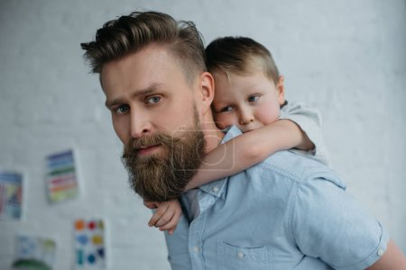 Photo for Side view of father and son piggybacking together at home - Royalty Free Image