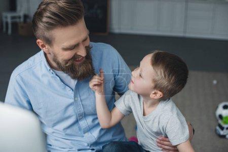 Photo pour Portrait d'un homme souriant et d'un petit fils se regardant à la maison - image libre de droit