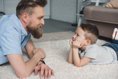 Photo pour Vue latérale du père barbu et du fils souriant se regardant à la maison - image libre de droit
