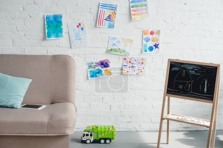 close up view of empty childish room with sofa, blackboard and toy truck on floor