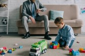 partial view of businessman  checking time while son playing with toys on floor at home, work and life balance concept