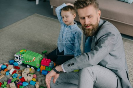 selective focus of pensive businessman in suit sitting near little son on floor at home, work and life balance concept