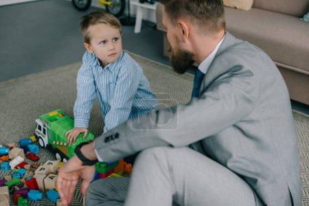 homme d'affaires en costume et petit garçon jouant avec des blocs colorés ensemble sur le plancher à la maison, travail et vie solde concept