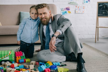 little boy hugging smiling father in business suit at home, work and life balance concept