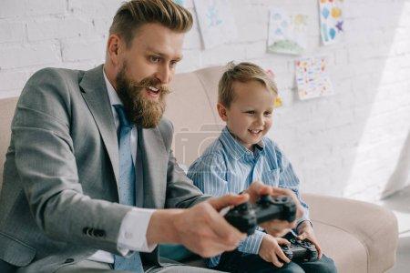 homme d'affaires et petit garçon jeux vidéo ensemble à la maison, travail et vie balance concept
