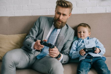 businessman and little son playing video games together at home, work and life balance concept