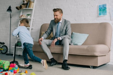 businessman in suit and little son on scooter at home, work and life balance concept