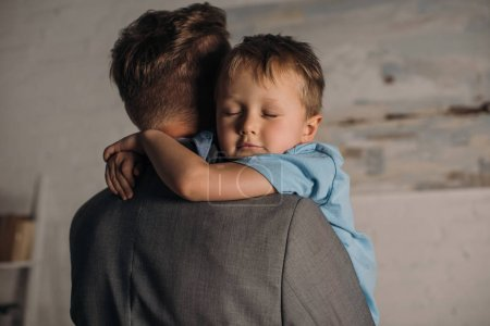 Photo for Little boy with eyes closed hugging father at home - Royalty Free Image