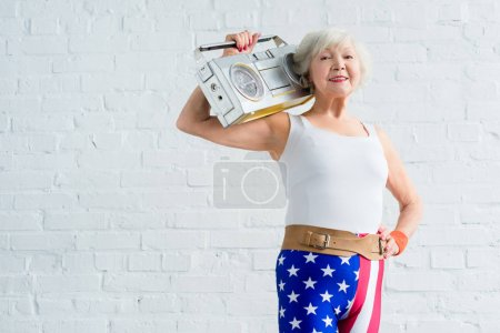 happy senior sportswoman holding tape recorder and smiling at camera