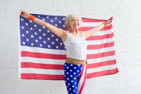 happy senior woman in sportswear holding american flag and smiling at camera