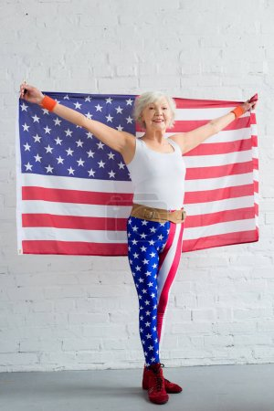 happy senior sportswoman holding american flag and smiling at camera