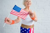 close-up view of happy senior sportswoman holding american flag and smiling at camera