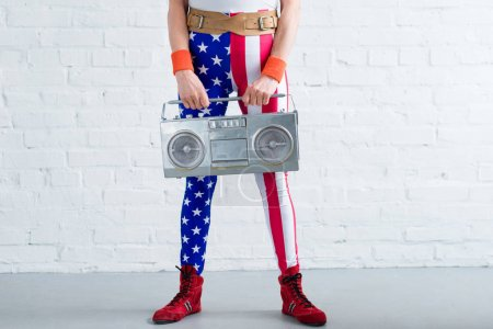 cropped shot of senior woman in patriotic sportswear holding tape recorder