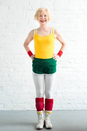 happy senior woman in sportswear standing with hands on waist and smiling at camera