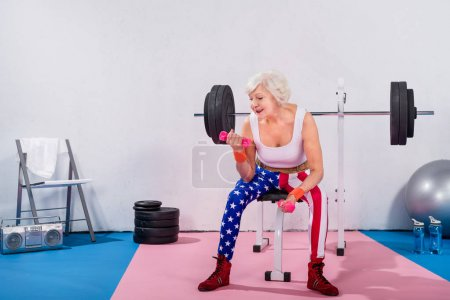 smiling senior woman in sportswear sitting and training with dumbbells in gym