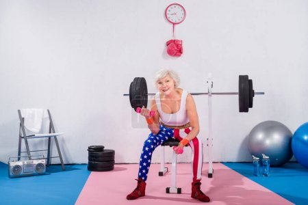 sporty senior lady exercising with dumbbells and smiling at camera