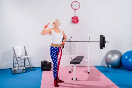 sporty senior lady in patriotic sportswear showing muscles and smiling at camera