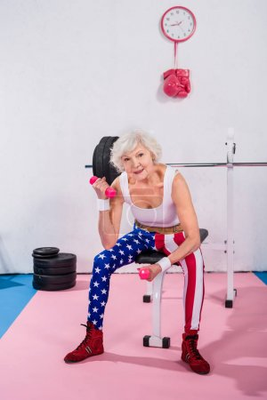 happy sporty senior woman exercising with dumbbells and smiling at camera