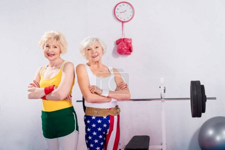 Photo for Senior sportswomen standing with crossed arms and smiling at camera in gym - Royalty Free Image