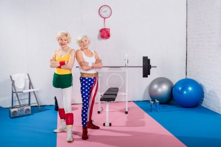 beautiful senior sportswomen standing with crossed arms and smiling at camera in gym
