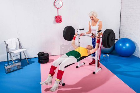sporive senior women exercising with barbell in gym