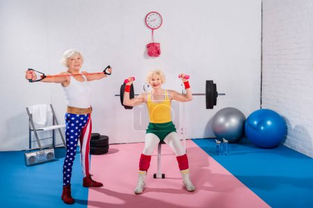 sporty senior women exercising and smiling at camera in gym