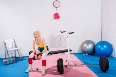 senior sporty woman sitting and smiling at camera in gym