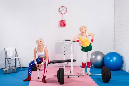 Photo for Happy sportive senior ladies in sportswear smiling at camera in gym - Royalty Free Image
