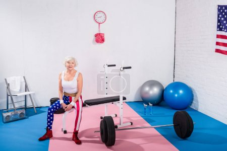 high angle view of senior sporty woman sitting and smiling at camera in gym