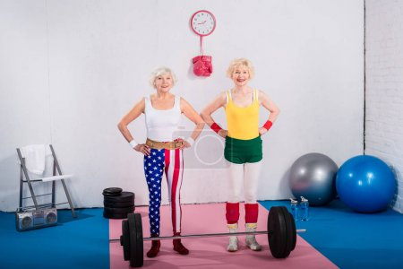 happy sporty senior women standing with hands on waist and smiling at camera in gym