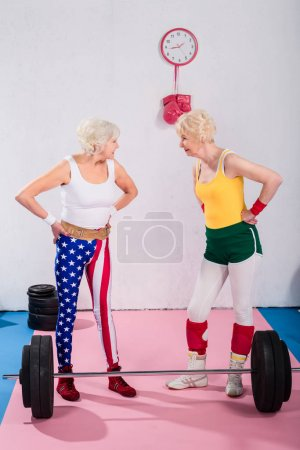 senior sportswomen standing with hands on waist and smiling each other in gym