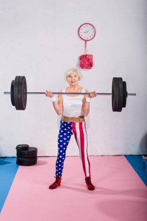 happy sporty patriotic senior woman lifting barbell and smiling at camera