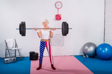 sporty senior lady lifting barbell and looking at camera