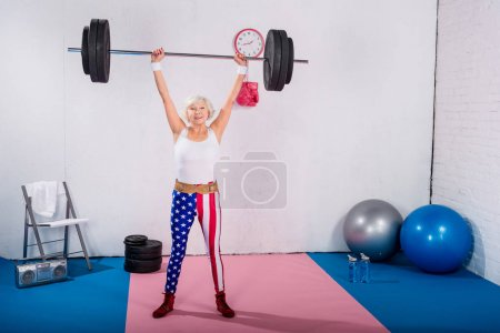 sportive senior woman lifting barbell and smiling at camera