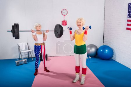 smiling senior sportswomen exercising with dumbbells and barbell in gym