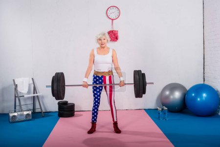 patriotic senior sportswoman lifting barbell and smiling at camera