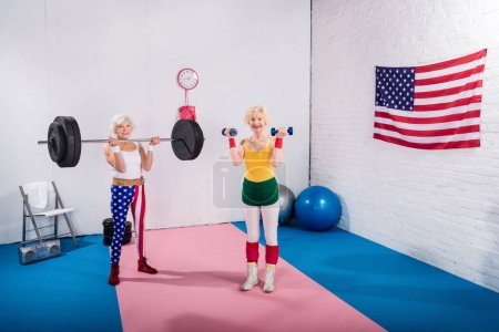 high angle view of smiling senior sportswomen exercising with dumbbells and barbell in gym