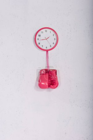 pink boxing gloves hanging at pink wall clock on white