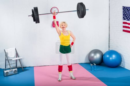 high angle view of senior sportswoman lifting barbell and smiling at camera