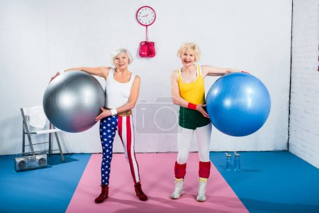 Photo for Sportive senior ladies holding fitness balls and smiling at camera in gym - Royalty Free Image