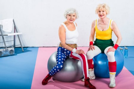 sporty senior ladies in sportswear sitting on fitness balls and smiling at camera