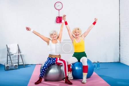 Photo for Happy senior sportswomen sitting on fitness balls and smiling at camera - Royalty Free Image