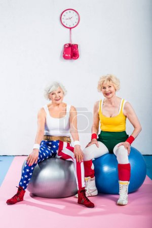 Photo for Sporty senior women in sportswear sitting on fitness balls and smiling at camera - Royalty Free Image
