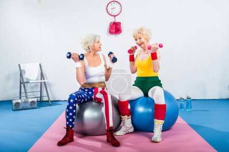 senior women in sportswear training with dumbbells while sitting on fitness balls and smiling each other
