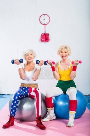 Photo for Senior women in sportswear training with dumbbells while sitting on fitness balls and smiling at camera - Royalty Free Image