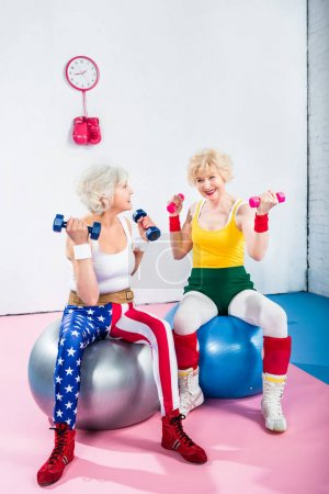 Photo for Smiling senior women in sportswear training with dumbbells and sitting on fitness balls - Royalty Free Image