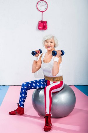happy sporty senior woman with dumbbells sitting on fitness ball and smiling at camera