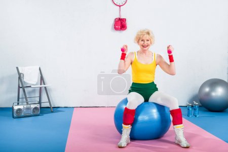 smiling sportive senior woman sitting on fitness ball and exercising with dumbbells